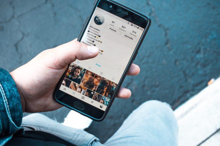 Girl holding phone on Instagram